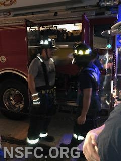Lt Kuseian reviews equipment in the rear compartment of Ladder 41 with Probationary Member Yaman Tobaje
