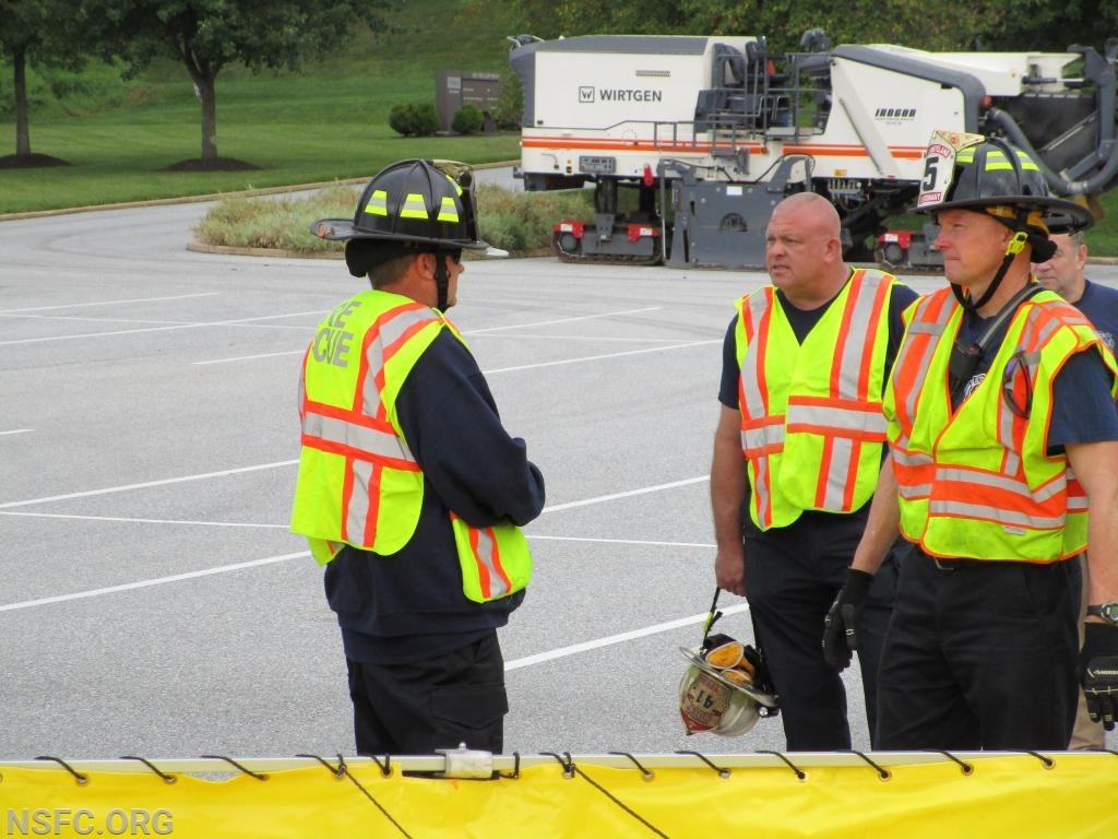 Career Staff Firefighter Brinkmann conversing with Assistant Chief Young on Dump Site Setup.